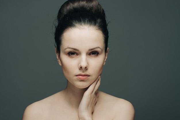 Épaules nues de femme et fond sombre de charme de peau claire. photo de haute qualité