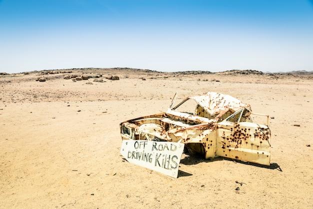 Épave de voiture dans le désert de namibie - panneau de danger sur la conduite hors route