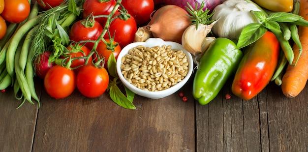 Épeautre dans un bol et légumes frais sur une table en bois brun close up