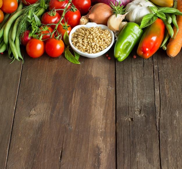 Épeautre dans un bol et légumes frais sur table en bois close up with copy space