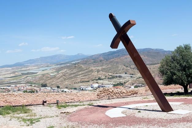 Épée de fer géante plantée dans le sol pour donner l'heure avec le cadran solaire d'ombre