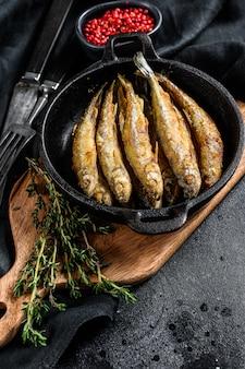 Éperlan frit dans la poêle sur la table avec des tomates et du poivre. fond noir. vue de dessus.