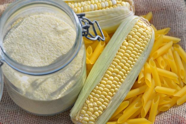 Épi frais de maïs et de farine dans un bocal de pâtes sans gluten sur du tissu