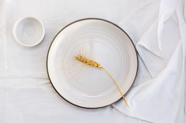 Un épi de grain sur une assiette vide sur la table. vue de dessus