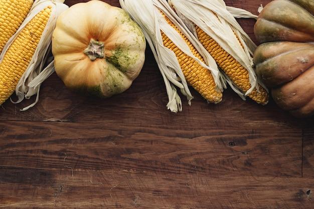 Épi de maïs et citrouille sur planche de bois brun close up
