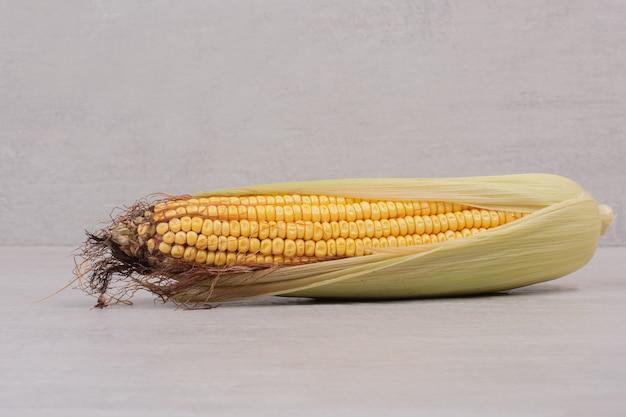 Épi de maïs frais sur blanc.