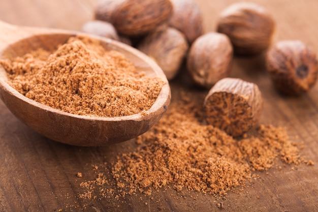 Épice de muscade moulue dans le plan rapproché de cuillère en bois