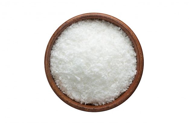 Épice de poudre de noix de coco dans un bol en bois, isolé sur blanc. vue de dessus d'assaisonnement