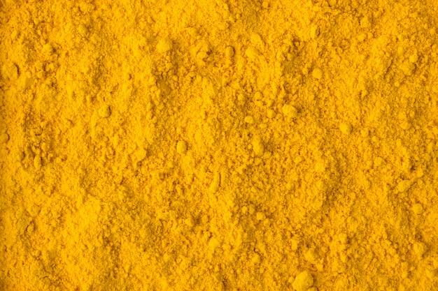 Épice en poudre de safran comme arrière-plan, texture d'assaisonnement naturel