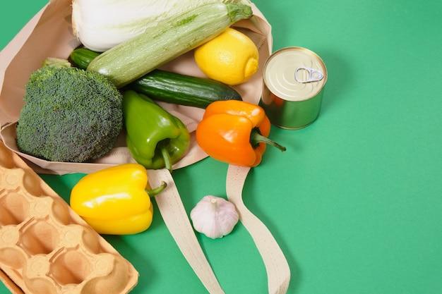 Épicerie en sac écologique en tissu sur la surface verte vue de dessus concept de mode de vie zéro déchet