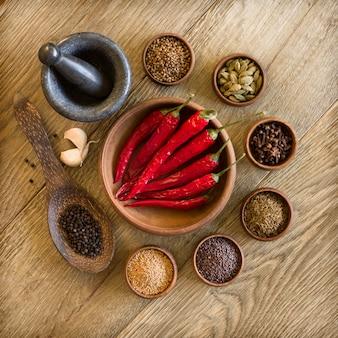 Épices, ail et poivron rouge dans des bols en bois