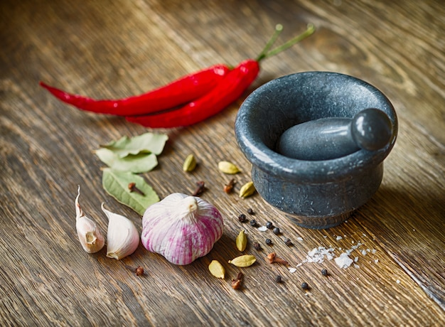 Épices, ail et poivron rouge sur une table en bois