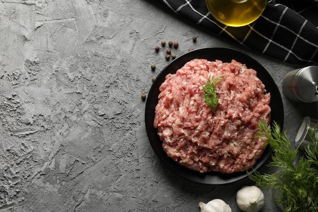 Épices et assiette de viande hachée sur fond gris, vue du dessus