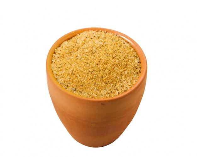 Épices au curry dans un bol en argile sur fond blanc