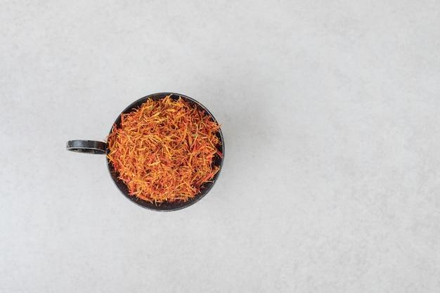 Épices au safran dans une tasse en céramique sur béton.
