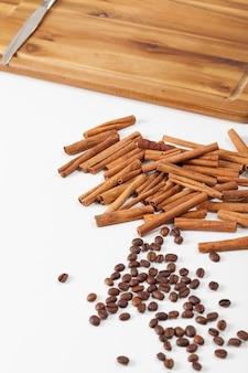 Épices de café et de cannelle dispersées sur un tableau blanc, nourriture naturelle