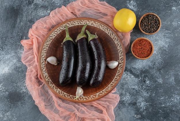 Épices chaudes, citron et aubergines crues fraîches sur fond gris.