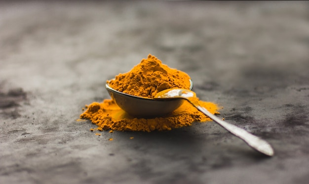 Épices curcuma dans une assiette sur un fond sombre, assaisonnements et herbes, médecine naturelle de l'inde