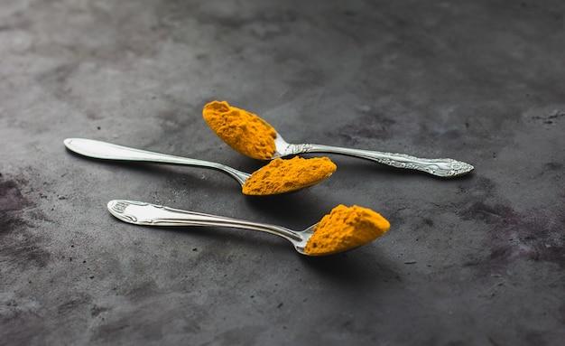 Épices de curcuma dans une cuillère sur fond sombre, assaisonnements et aliments sains