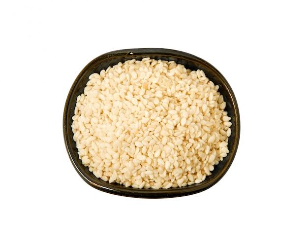 Épices dans un bol d'argile sombre sur fond blanc
