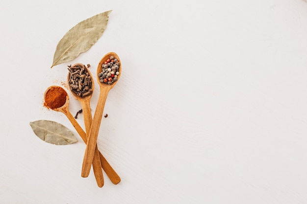 Épices dans une cuillère en bois. herbes, curry, safran, curcuma, cannelle, laurier, poivrons pour la cuisson sur fond blanc