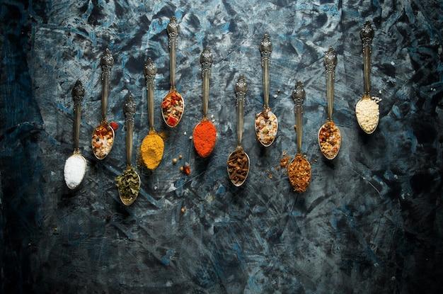 Épices dans une cuillère sur une surface sombre.