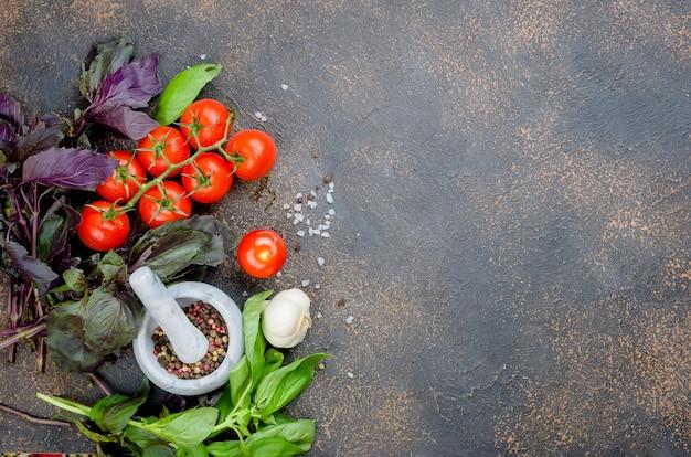 Epices dans un mortier de pierre, basilic vert et tomates