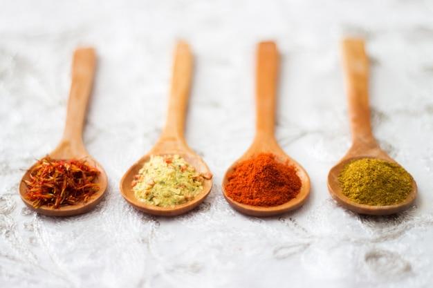 Épices. épice en cuillère en bois. herbes. curry, safran, curcuma,