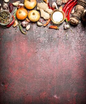 Épices fraîches. une variété d'épices aromatiques avec des piments et des oignons sur une table rustique.