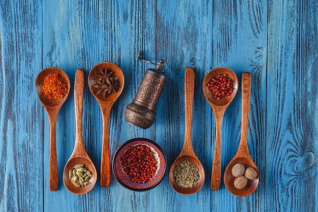 Épices et herbes colorées sur des cuillères rustiques