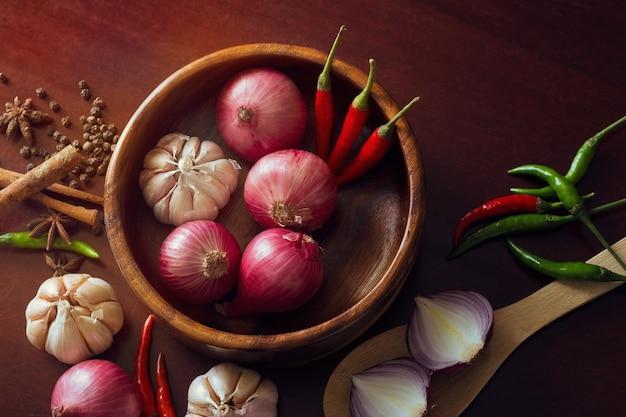 Épices d'herbes fraîches, tranches d'oignon, ail et piments dispersés sur la surface en bois