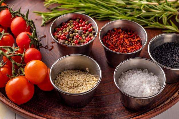 Épices: un mélange de poivrons, de flocons de paprika, de sel de mer, de sésame noir et blanc, de romarin et de tomates cerises sur une assiette en gros plan