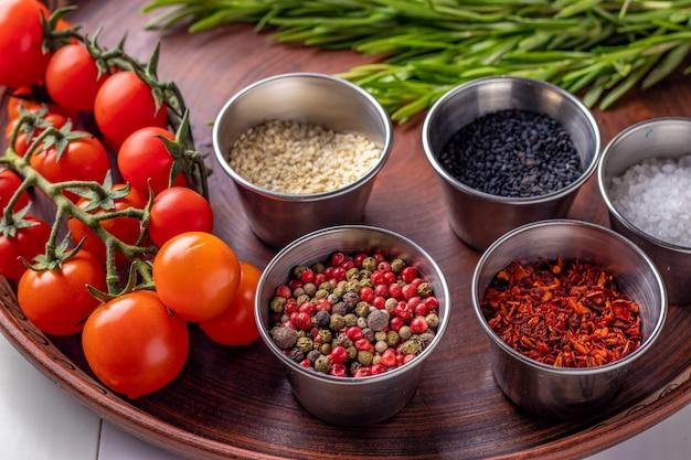 Épices: un mélange de poivrons, flocons de paprika, sel de mer, sésame noir et blanc, romarin et tomates cerises sur une plaque en gros plan