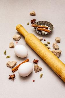 Épices, œufs, sucre brun en morceaux, plat de cuisson pour cupcakes et rouleau à pâtisserie. lumière