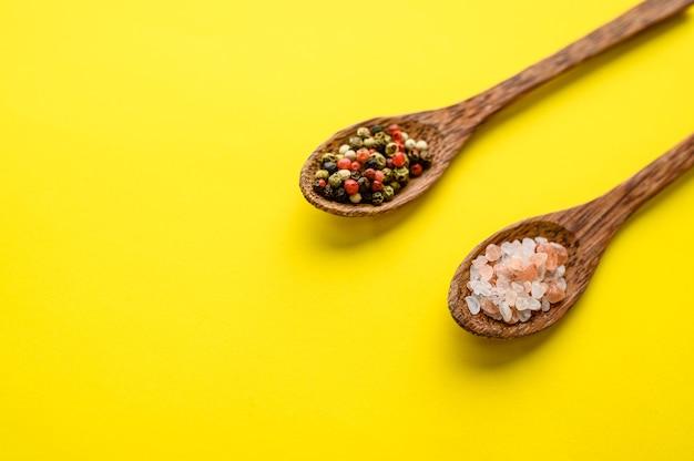 Épices parfumées dans une cuillère et poivron rouge isolé sur fond jaune, vue du dessus. nourriture végétarienne biologique, assortiment d'épicerie, produits écologiques naturels, concept de mode de vie sain
