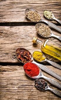 Épices parfumées dans des cuillères avec une bouteille d'huile d'olive sur table en bois. vue de dessus