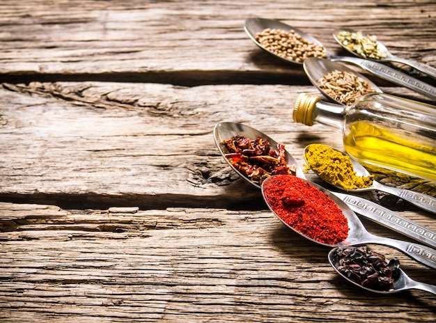 Épices parfumées dans des cuillères avec une bouteille d'huile d'olive sur table en bois.