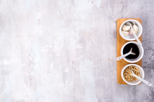 Épices, pignons de pin, sauce soja et ail sur un bol, fond de pierre grise avec espace de copie