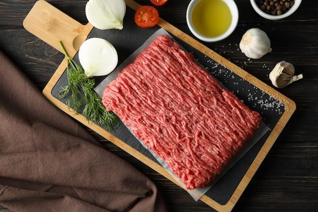 Épices et planche à découper avec de la viande hachée sur bois, vue de dessus