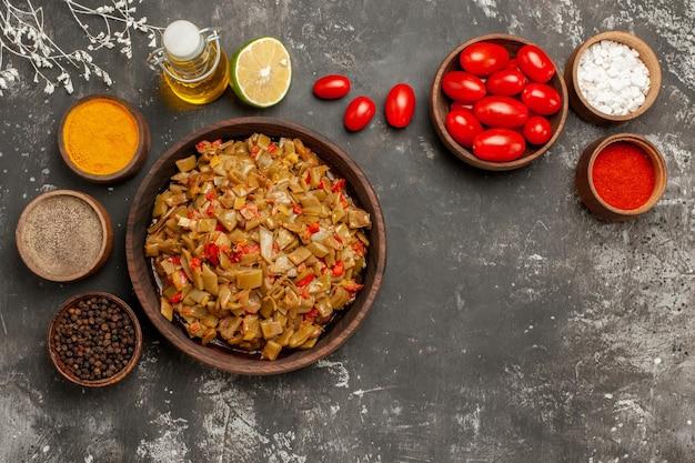 Épices et plats épices bouteille d'huile citron et tomates à côté de l'assiette de haricots verts
