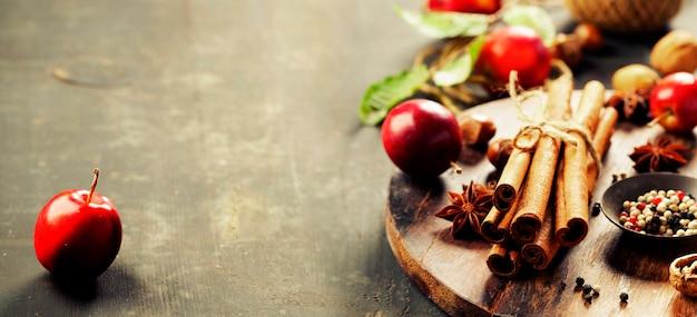 Épices et pommes sur une table rustique, composition horizontale