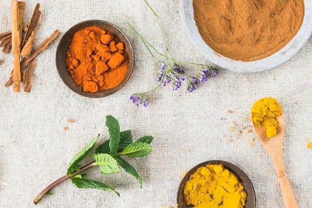 Épices près de cannelle et brindille de plante sur textile sur table