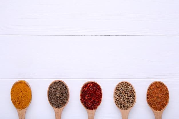 Les épices se mélangent sur des cuillères en bois sur un fond en bois blanc. vue de dessus
