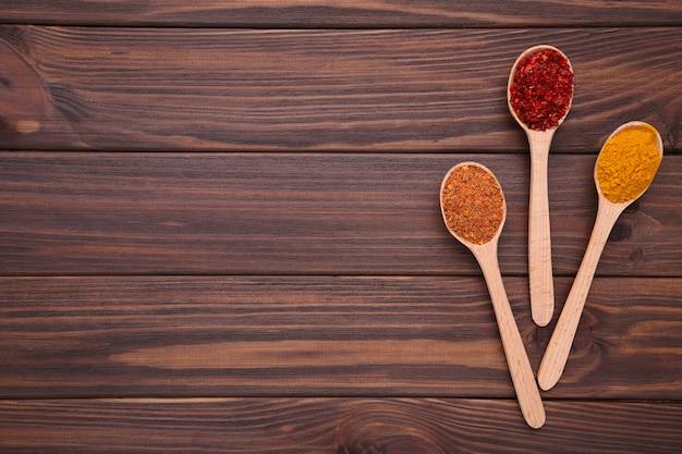 Les épices se mélangent sur des cuillères en bois sur un fond en bois marron. vue de dessus