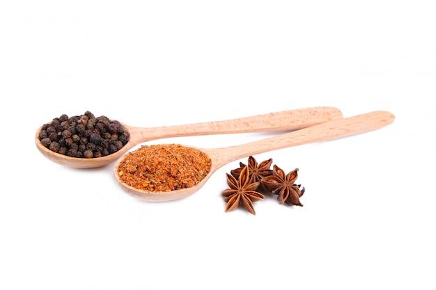 Les épices se mélangent sur des cuillères en bois, isolés sur fond blanc. vue de dessus