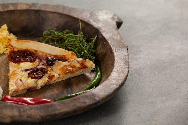 Épices et tranche de pizza italienne dans un bol en bois