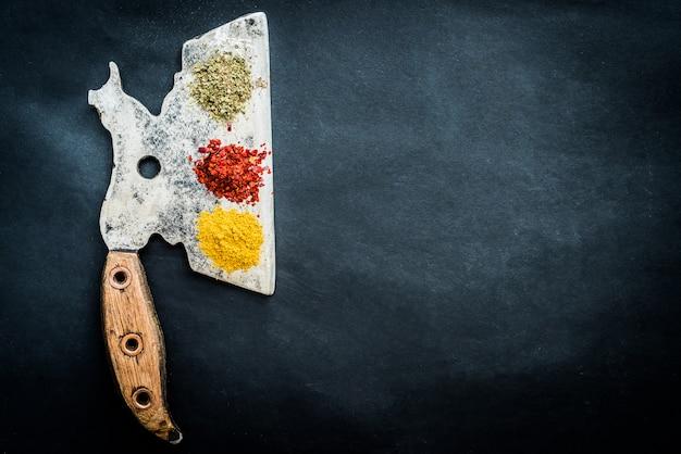 Épices avec vieille hache de cuisine