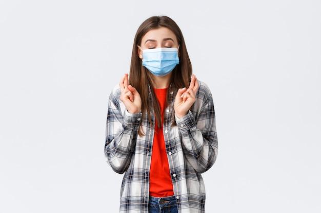Épidémie de coronavirus, loisirs en quarantaine, éloignement social et concept d'émotions. espoir mignon jeune femme en masque médical priant, fermer les yeux et croiser les doigts bonne chance, faire voeu