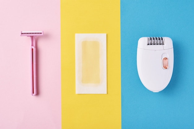 Épilateur, rasoir et bandes de cire sur fond de couleur