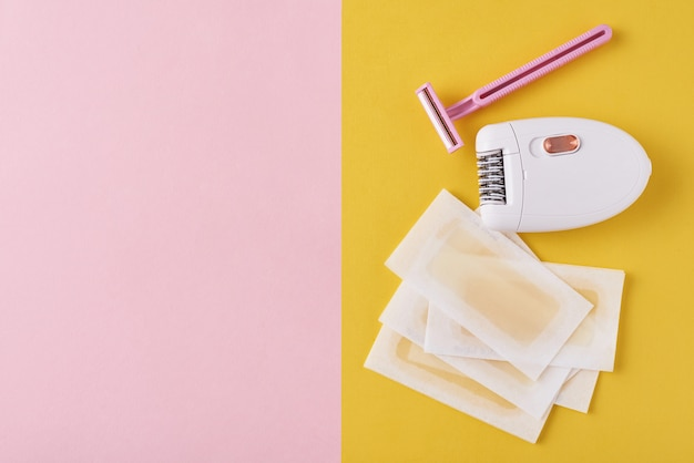 Épilateur, rasoir et bandes de cire sur fond jaune et rose